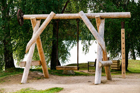The wooden swing is made of thick round beams