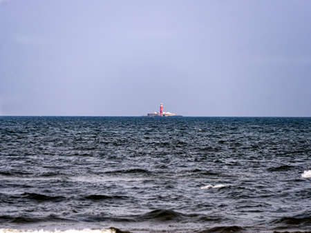 Far out in the sea rises a lighthouse emitting light for ships.Latvia, Cape Kolka, 22 September 2020