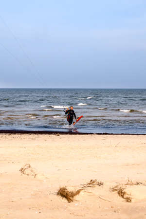 A young man is engaged in extreme kiteboarding in the Gulf of Riga on October 21, 2019 at Cape Kolka in Latvia