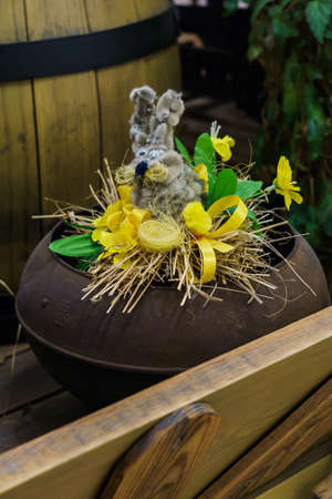Easter composition of willow in the form of a hare and flowers in a cast iron Reklamní fotografie