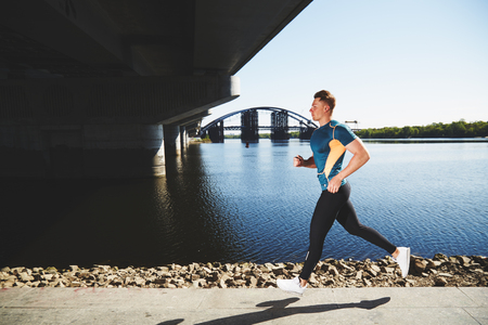 man t shirt: Young handsome man running along the embankment near the river under the bridge