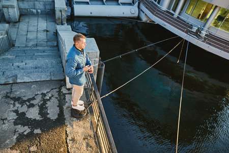 chinos: Man casting with light rod on the river near the dock