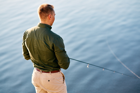 chinos: Man casting with light rod on the river against the water surface