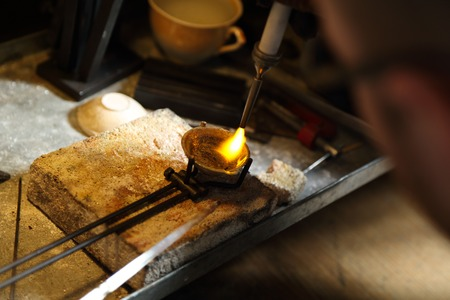 precious metal: Jeweler melting precious metal with hydrogen burner Stock Photo