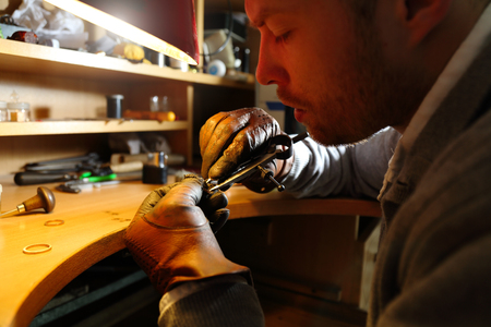 lith: Jeweler measuring a ring with compass divider in a workshop lith with warm light Stock Photo