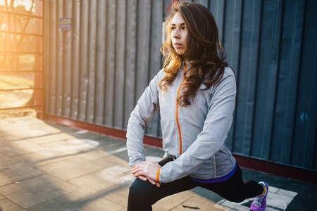 lunges: Young beautiful sporty woman doing lunges outdoors in a park Stock Photo