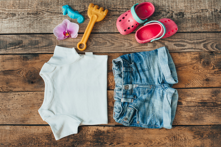 clogs: Overhead view of child clothes laid out on a rustic wood tabletop, including shorts, t-shirt, toys, clogs, orchid flower