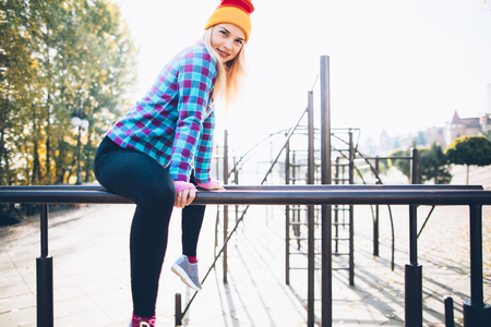 calisthenics: Young beautiful woman relaxing during street workout sitting on parallel bars at calisthenics park, looking at camera Stock Photo