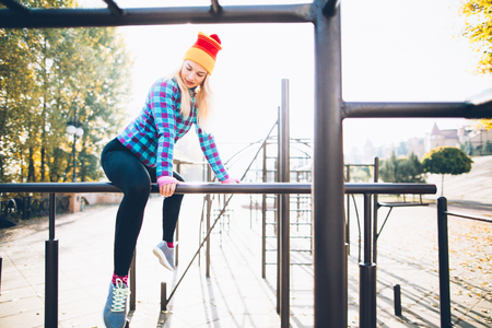 calisthenics: Young beautiful woman relaxing during street workout sitting on parallel bars at calisthenics park, looking off the camera