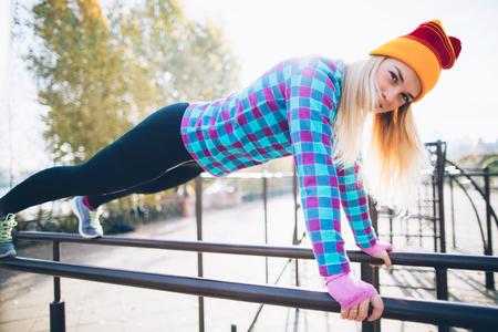 calisthenics: Young beautiful woman doing push ups on parallel bars at calisthenics park, looking at the camera
