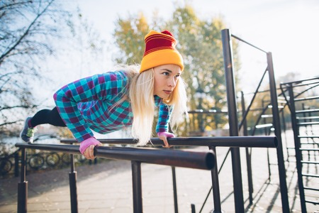 calisthenics: Young beautiful woman doing push ups on parallel bars at calisthenics park, looking off the camera Stock Photo