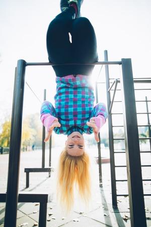 calisthenics: Young beautiful woman hanging upside down on horizontal bar at calisthenics park, looking at the camera giving thumbs up Stock Photo