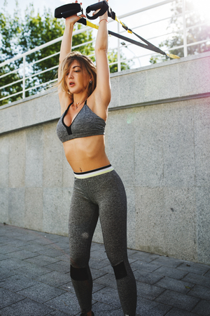 Young beautiful woman working out with suspension trx straps