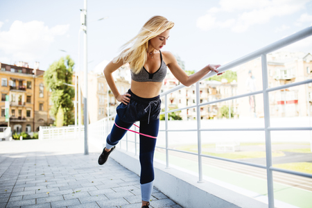 Young beautiful woman working out with rubber resistance bands Stock Photo