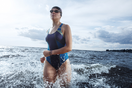 Young woman in swimsuit running in the water
