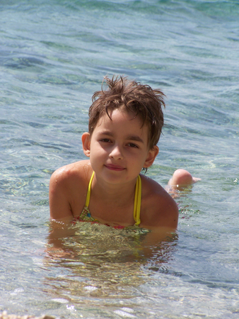 swimming suit: Little girl in a swimming suit swimming in the sea, looking to the camera