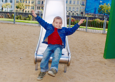 lifted hands: Cute little boy on a slide