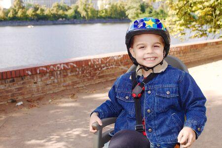 helmet seat: Little boy with a helmet sitting on a bike seat