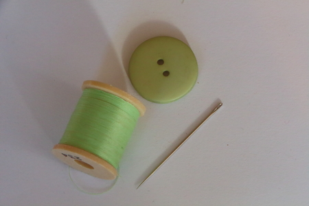 Reel of green thread for sewing, needle and green button Stock Photo