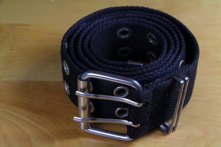 Black fabric belt wind up on a wooden table