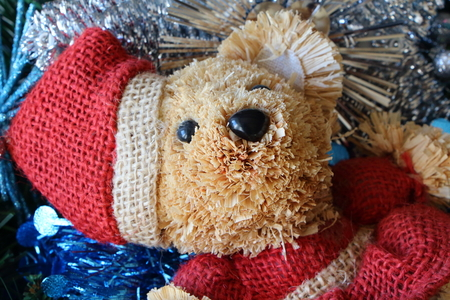 Santa Claus teddy bear, silvery Christmas balls and blue tinsel on a Christmas wreath