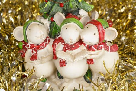 Mouses figurines singing for Christmas and golden tinsel