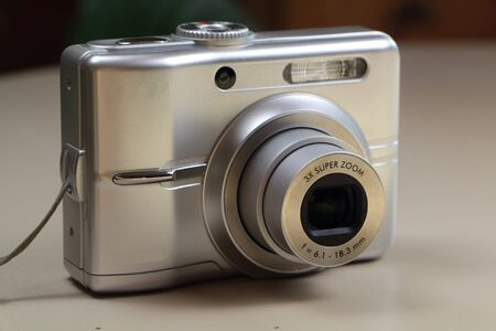 Silvery compact digital camera with zoom out