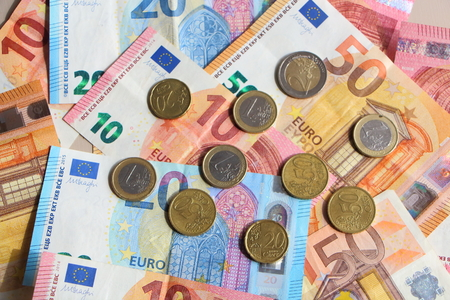 Euro coins on banknotes of ten, twenty and fifty euros spread on a table Stockfoto