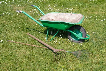 Green wheelbarrow with lawn rake and claw cultivator for cleaning of a garden Stockfoto