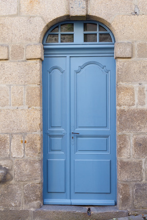 Blue wooden door of an old house in a wall made in stone Reklamní fotografie