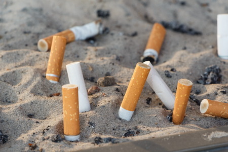 Cigarette butts crushed in the sand of an ashtray