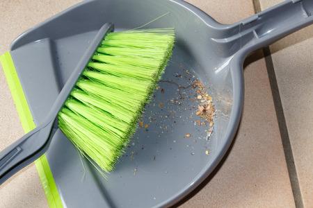Brush and dustpan with dust on the floor of an house Stockfoto
