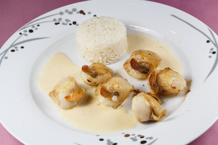 Plate of grilled scallops with rice and cream sauce