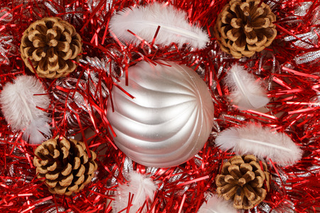 Pines cones, feather and silvery bauble on a red tinsel as decoration for Christmas 스톡 콘텐츠