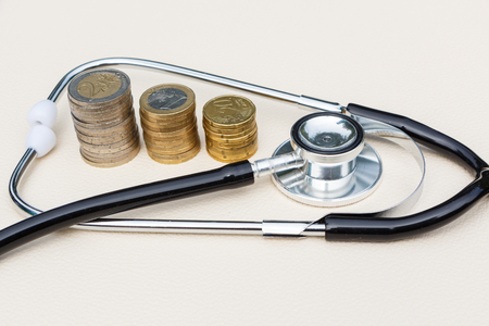 Black stethoscope and three heaps of euros coins Stock fotó
