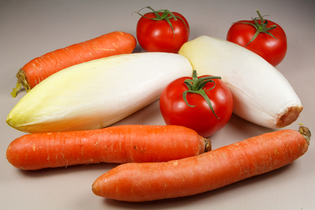 Raw fresh carrots, endives and tomatoes Archivio Fotografico