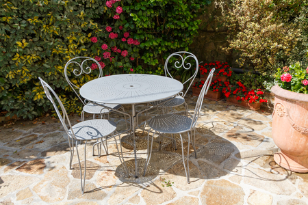 Flowered terrace with gray garden furniture made in wrought iron
