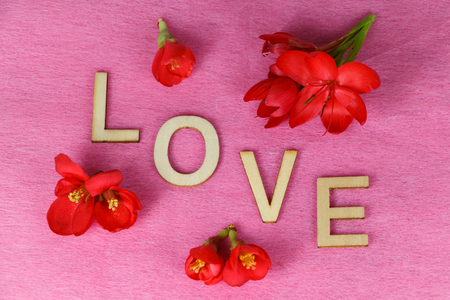 Red flowers and love written in wooden letters for Valentine's Day