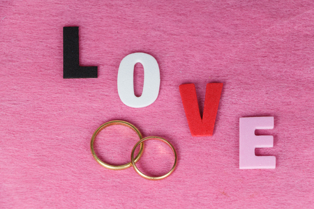 Two wedding rings and love written in colored letters for Valentines Day