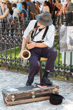 PRAGUE - CZECH REPUBLIC, AUGUST 14 : Old man playing saxophone in a street and people listening to him, August 14, 2017