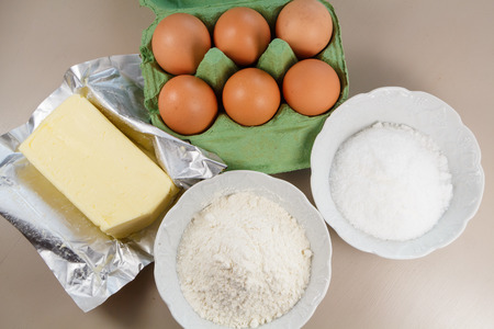 Ingredients to make a cake, eggs, butter, flour and sugar
