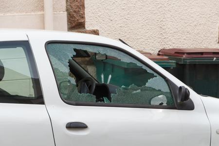 Broken window of a car parked in a street