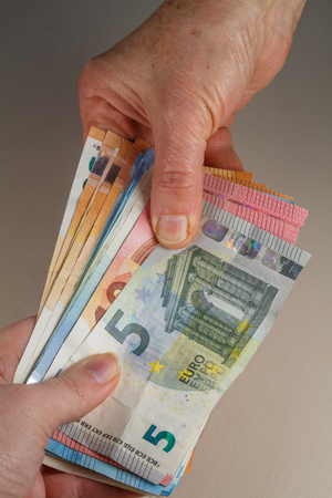 Hand of a woman holding euro banknotes to another person Reklamní fotografie