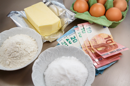 Ingredients to make a cake and banknotes of ten and twenty euros as illustration for the price of food