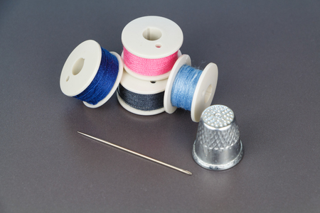 Four reels of thread of blue, pink and gray color for sewing, needle and thimble Banco de Imagens
