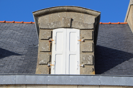 Dormer window with white closed shutter on the roof of an house