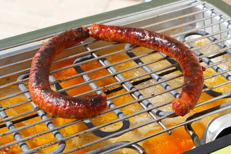 Merguez on the grid of an electric barbecue