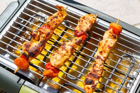 Marinated chicken brochette on electric barbecue Stok Fotoğraf