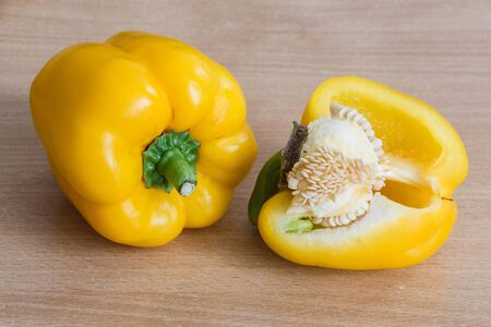 Yellow whole and half peppers on wooden background
