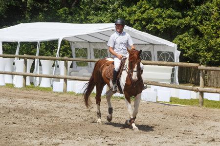 BREST, FRANCE - JUNE 28 : man riding a chestnut pinto horse, June 28, 2019 新聞圖片